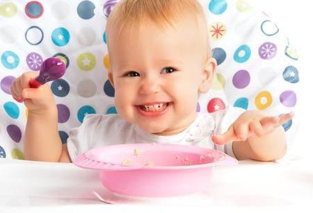 vrolijke gelukkige baby kind zelf eet met een lepel Stockfoto