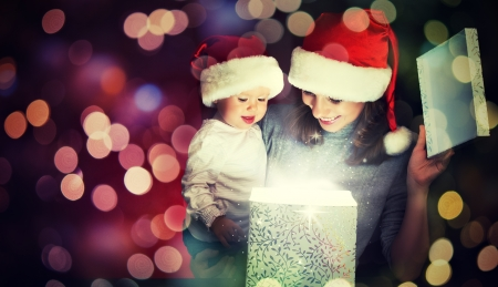 Christmas magic gift box and a woman happy family mother and Child baby photo