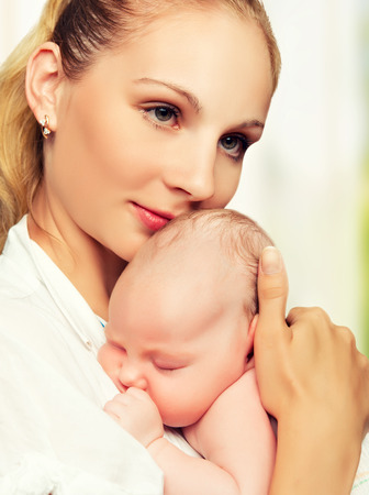 little newborn baby in the arms of mother photo