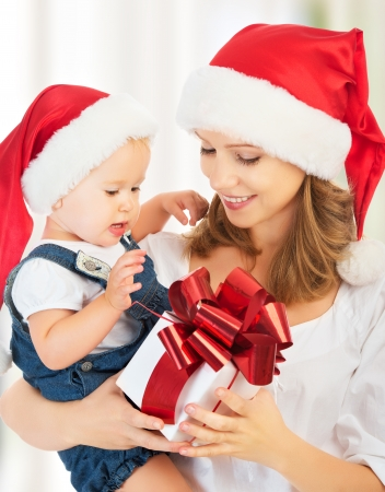happy family mother and baby with gift   in red Christmas hats