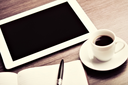 workplace, office desk: cap of coffee and tablet pc and notebook with pen  photo
