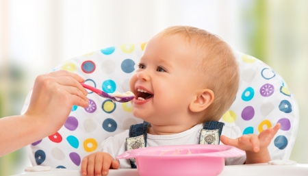 happy mother feeds funny baby from a spoon photo