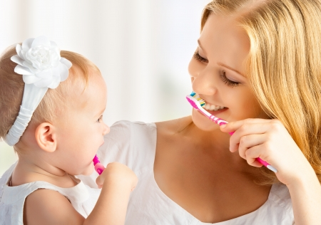 happy family and health. mother and daughter baby girl brushing their teeth together Reklamní fotografie