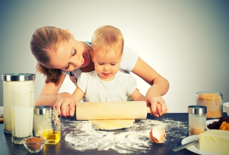baby girl with her mother rolled out the dough cook, bake photo