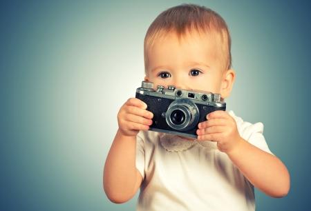 Beauty baby girl photographer with retro camera photo
