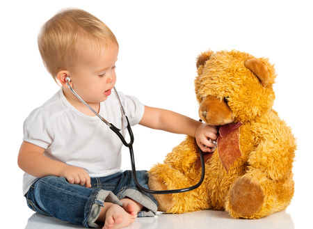 sick teddy bear: baby plays in doctor toy bear and stethoscope