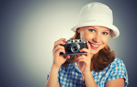 happy young female photographer with retro camera in a hat photo