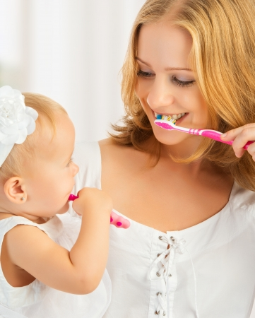 girl teeth: happy family and health. mother and daughter baby girl brushing their teeth together Stock Photo