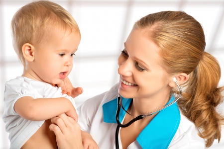 baby at the doctor pediatrician. doctor listens to the heart with a stethoscope