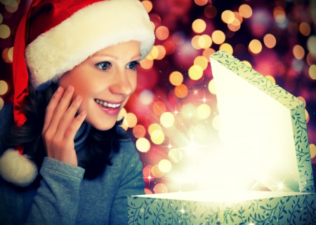 happy woman in a Christmas cap opens the magic box gift Stock Photo - 23181396