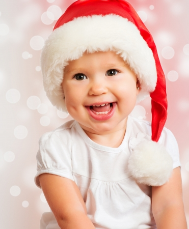 Beautiful funny baby in a Christmas hat  on pink background Stock Photo - 23181397