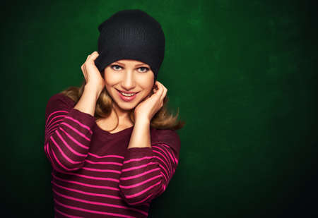 Young beautiful happy girl cheeky teenager in a black hat and a pink dress on a green background photo