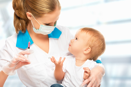 to inject: A doctor does injection child vaccination baby Stock Photo