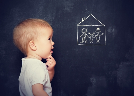 Concept baby looks at the board, which is drawn with chalk family and home photo