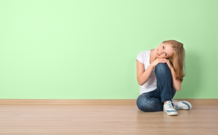 happy young woman is sitting in a room with a blank wall photo