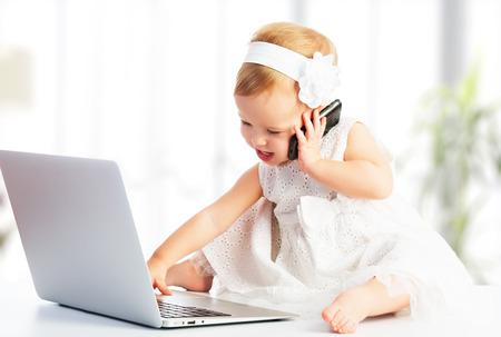 baby s: baby meisje met laptop en mobiele telefoon Stockfoto