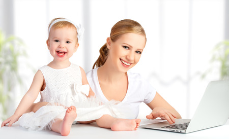maternity leave: happy family mother and baby at home using laptop computer Stock Photo