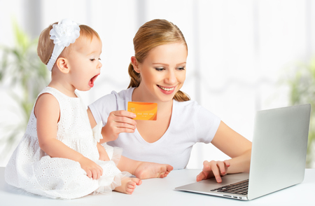 business casual: mother and baby make purchases over the Internet with a laptop and a credit card