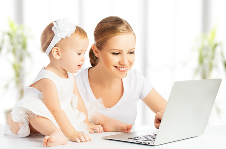 smiling mother: Mom and baby with laptop computer working from home