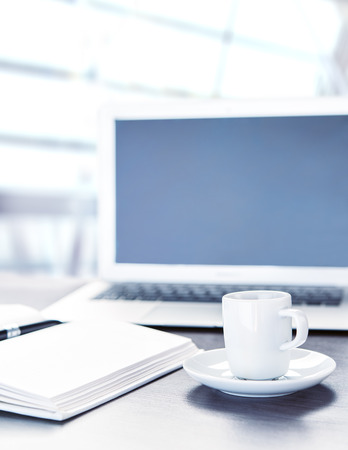 work office desk with a cup of coffee computer laptop, notebook, pen Stock Photo - 24220766