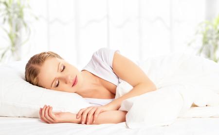persona: joven y bella mujer que duerme y sonríe en su sueño en la cama