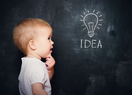 idea light bulb: baby child at the blackboard with chalk drawn light bulb symbol ideas Stock Photo