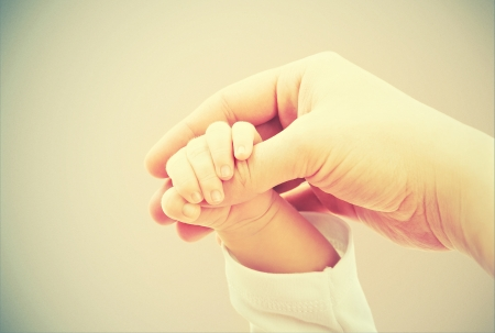 fond of children: concept of love and family. hands of mother and baby closeup Stock Photo