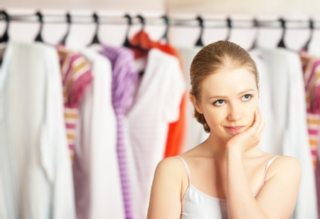 clothes closet: Young woman chooses clothes in the wardrobe closet at home