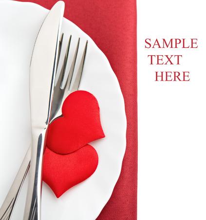 バレンタインの日のためのテーブルの設定。皿、フォーク、ナイフ、赤の心