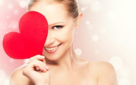 gezicht van een mooie jonge vrouw met rood hart symbool van de liefde Stockfoto