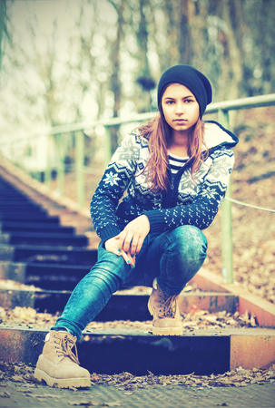 lonely girl teenager in hat sitting on stairs and sad autumn outdoors photo