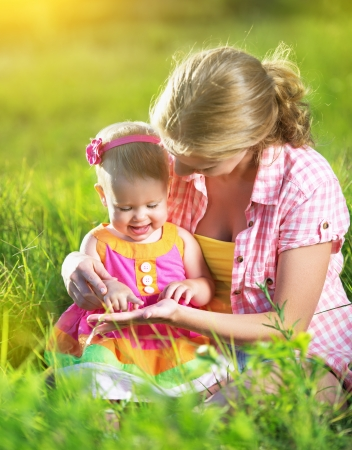 happy family. Mom and baby resting in a meadow in the summer outdoors in the park Stock Photo