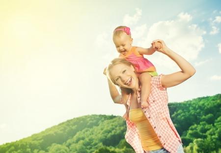 diversion: familia feliz. madre e hija bebé niña jugando en la naturaleza al aire libre