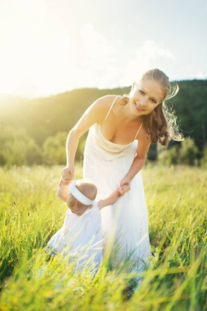 happy family on nature outdoors mother and baby daughter on the green meadow in a white dress photo