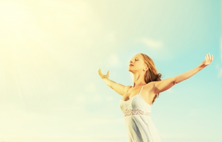 happy young woman open her arms to the sky and enjoying life photo