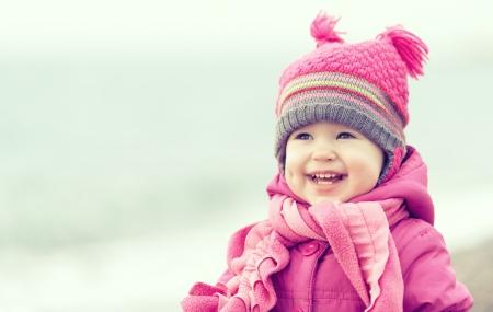 sweet baby girl: Beb� feliz en un sombrero de color rosa y se r�e de la bufanda