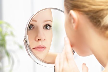 거울에 젊은 아름 다운 건강 한 여자와 반사의 얼굴 스톡 콘텐츠