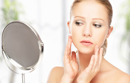 reflection in mirror: face of young beautiful healthy woman and reflection in the mirror Stock Photo