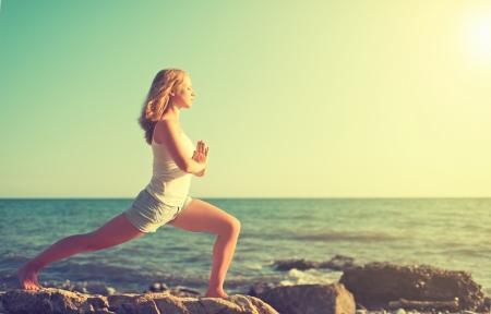 jonge vrouw doet yoga op de kust van de zee op het strand
