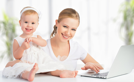 leave: happy family mother and baby at home using laptop computer Stock Photo