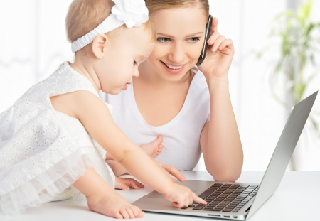 young mother with baby daughter works on the Internet with a computer and phone photo