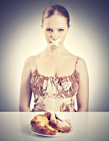 diet concept. woman mouth sealed with duct tape dreaming of biscuits and buns photo
