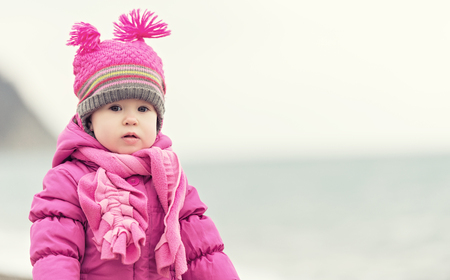 warm clothing: baby girl in a pink hat and scarf sad