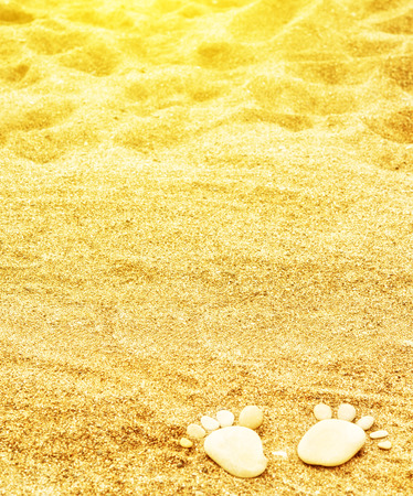 concept background. footprints of stones on yellow sand on the beach in summer photo