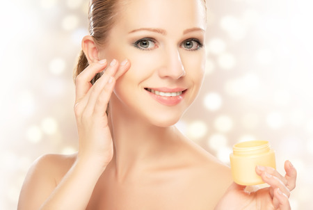 happy young beautiful woman using a face cream photo