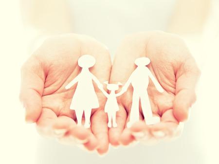 concepto. figuras de papel de la familia en las manos Foto de archivo