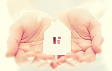 family business: concept. paper figurine house in the hands Stock Photo