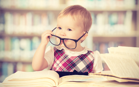 child studying: Happy funny baby girl in glasses reading a book in a library Stock Photo