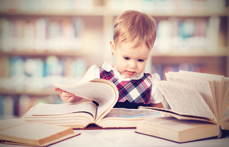 Happy cute baby girl reading a book in a library Stok Fotoğraf - 26519482