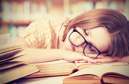 tired student girl with glasses sleeping on the books in the library Фото со стока
